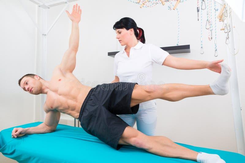 Fisioterapeuta que exercita com paciente na prática imagem de stock
