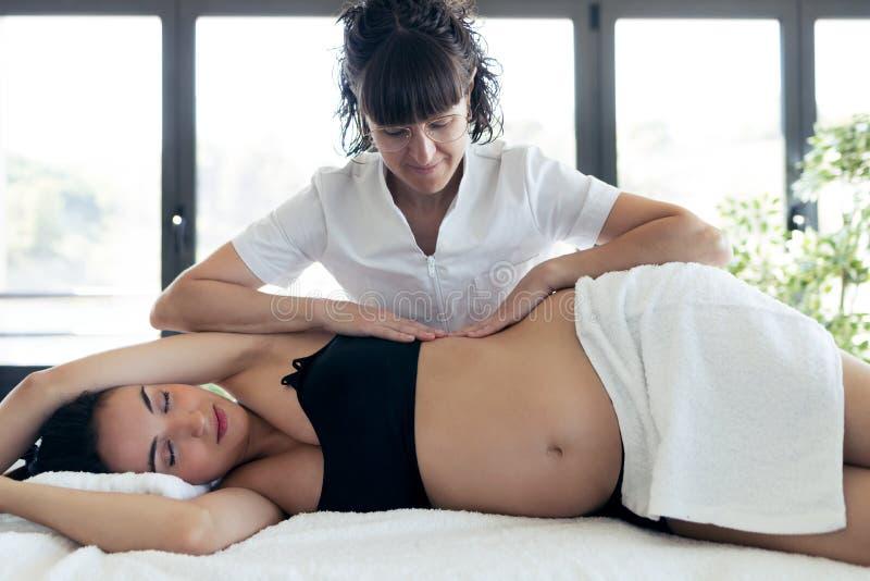Fisioterapeuta que faz a massagem da barriga à mulher gravida bonita no centro dos termas fotografia de stock