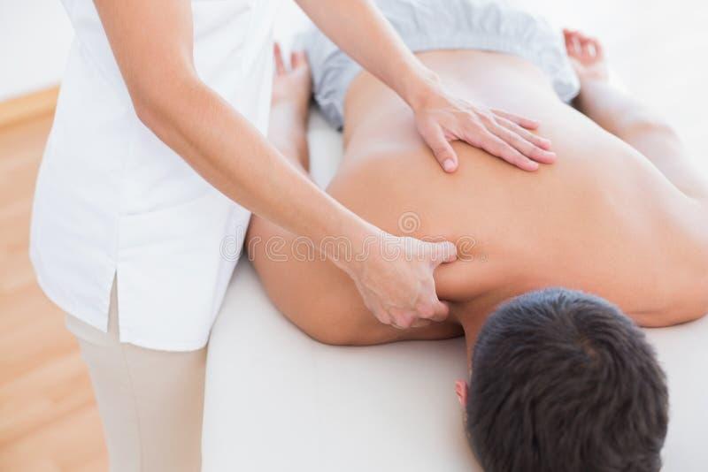 Fisioterapeuta que faz a massagem do ombro a seu paciente imagem de stock