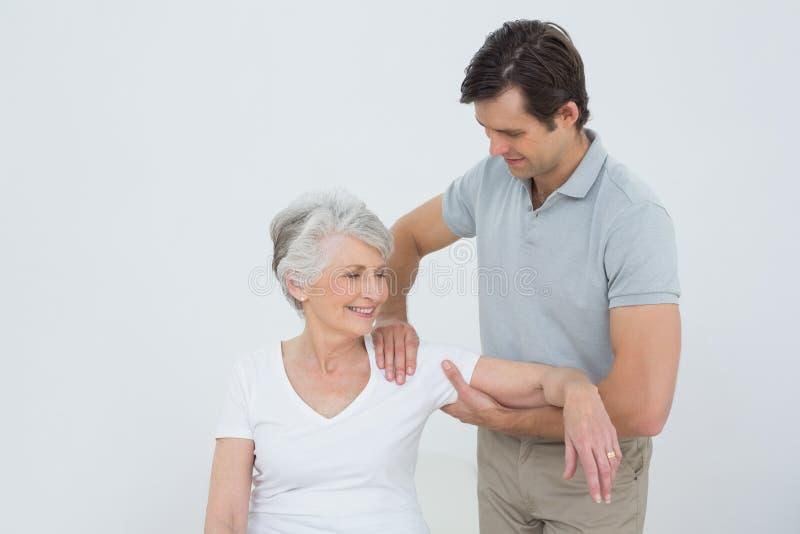 Fisioterapeuta que faz massagens o braço de uma mulher superior de sorriso fotos de stock royalty free