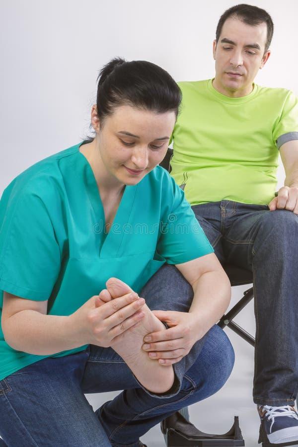 Fisioterapeuta que faz massagens o pé do homem novo na cadeira de rodas foto de stock