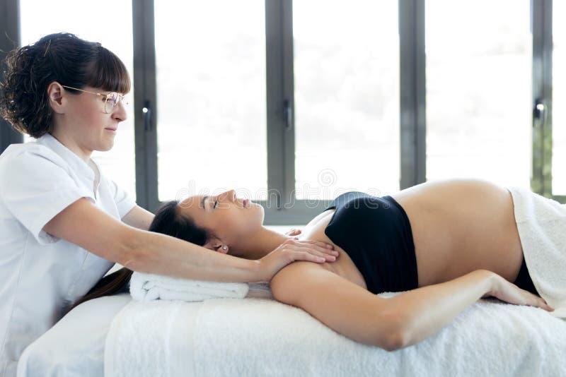 Fisioterapeuta que faz massagens os ombros da mulher gravida no centro dos termas fotografia de stock