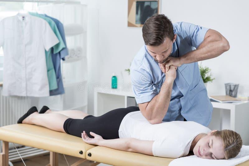 Fisioterapeuta que faz massagens a parte traseira da mulher imagens de stock