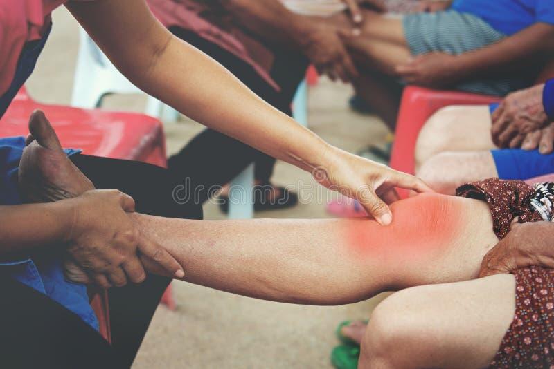 Fisioterapeuta que hace la cura en dolor paciente de la rodilla imagen de archivo libre de regalías