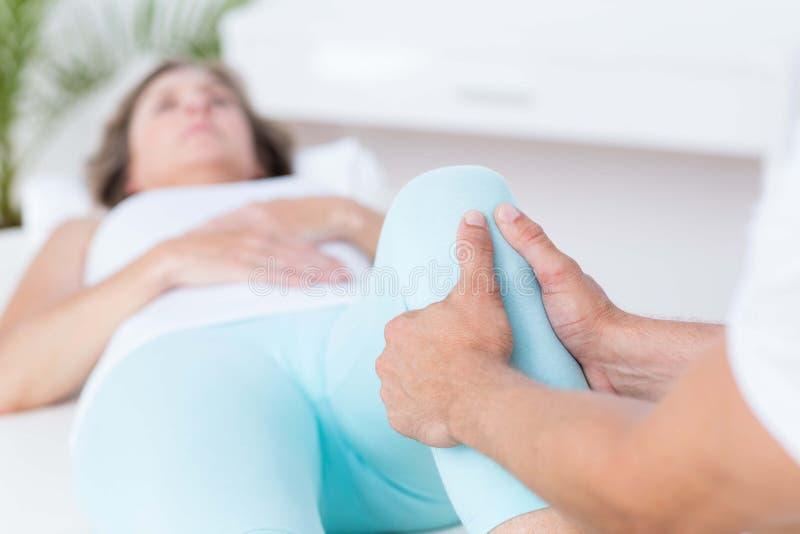 Fisioterapeuta que hace masaje de la pierna a su paciente foto de archivo libre de regalías