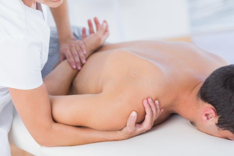 Fisioterapeuta que hace masaje del hombro a su paciente fotos de archivo