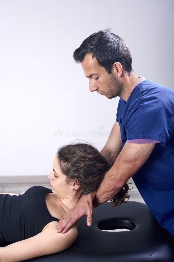 Fisioterapeuta que hace un cuello de la movilizaci?n del paciente femenino Terapia manual Examen f?sico neurol?gico Osteopat?a, imagen de archivo libre de regalías