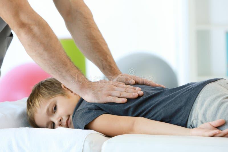 Fisioterapeuta que trabaja con el paciente en clínica, imagen de archivo