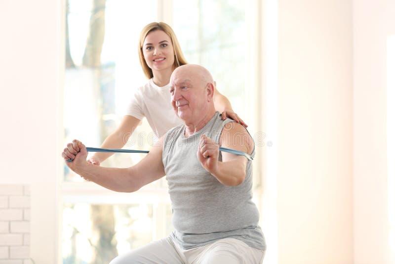 Fisioterapeuta que trabaja con el paciente mayor en clínica foto de archivo
