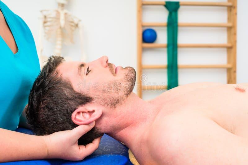 Fisioterapeuta que trata al hombre desnudo-de pecho joven en el sofá imagen de archivo libre de regalías