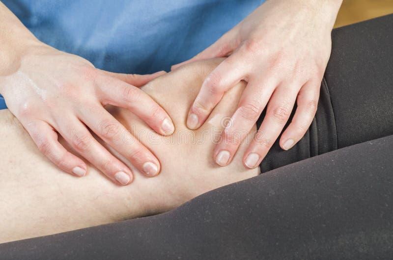 Fisioterapeuta, quiropráctico que hace una movilización patelar, dolor de la rodilla Ligamentos rasgados que tuercen fotos de archivo libres de regalías