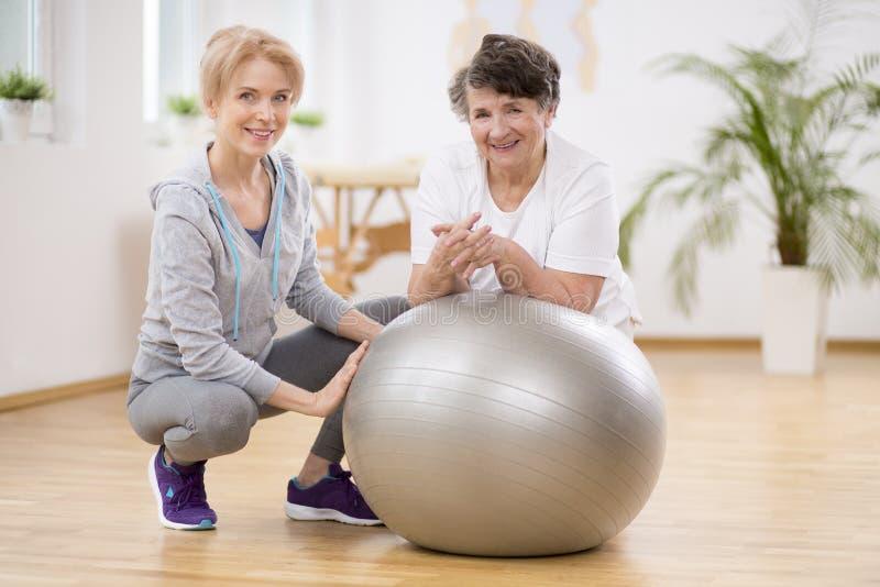 Fisioterapeuta sonriente con la mujer mayor que pone en el ejercicio de la bola durante terapia física foto de archivo libre de regalías