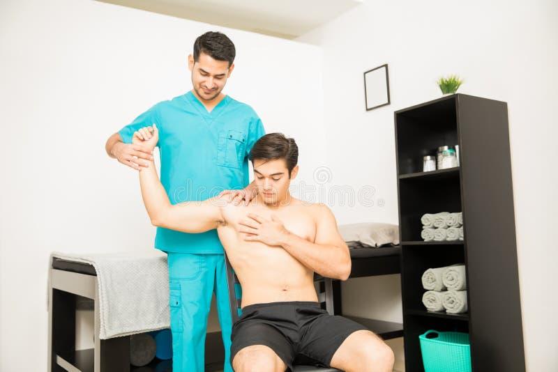Fisioterapeuta Treating Shirtless Man que sufre del hombro A foto de archivo