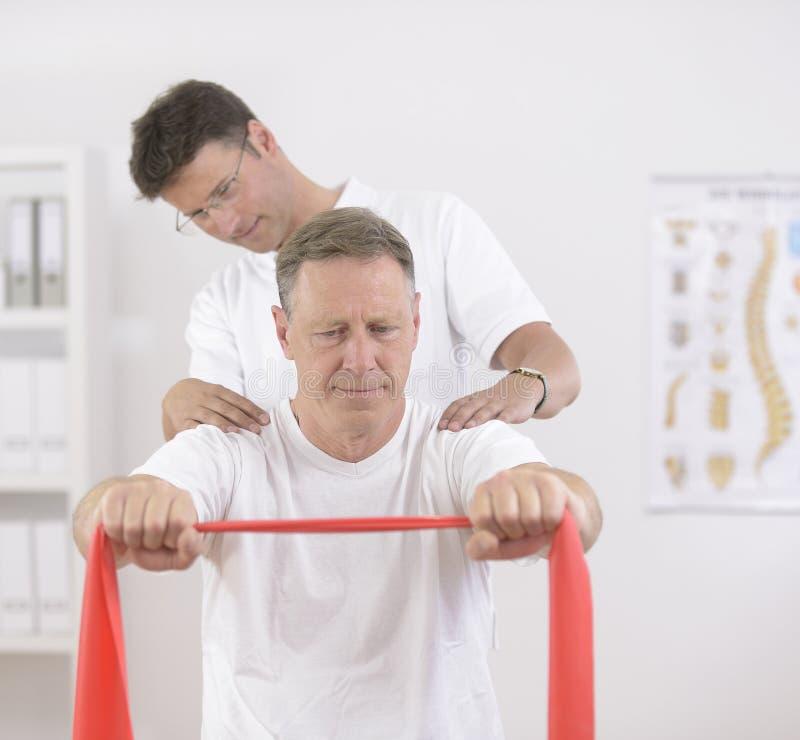 Fisioterapia: Hombre mayor y fisioterapeuta fotografía de archivo