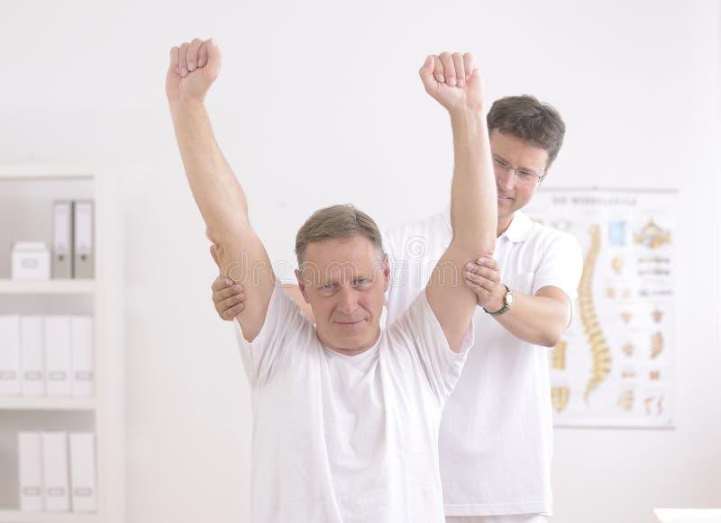 Fisioterapia: Hombre mayor y fisioterapeuta fotos de archivo libres de regalías