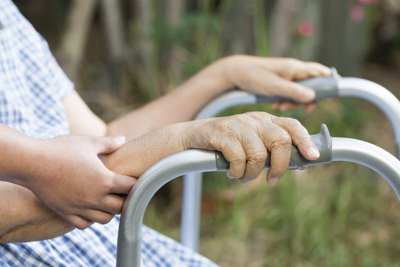 Fisioterapia idosa pelo cuidador no quintal fotografia de stock