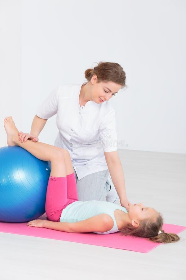 Fisioterapia pediatra profissional com bolas do exercício fotografia de stock