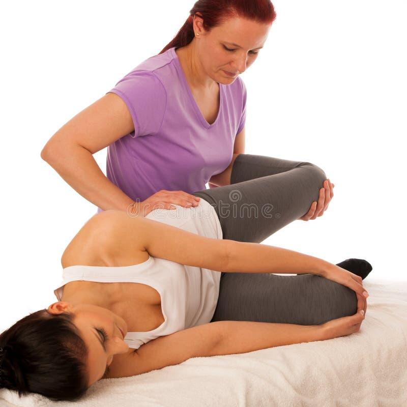 Fisioterapia - terapeuta que excercising com o paciente, trabalhando em l foto de stock royalty free