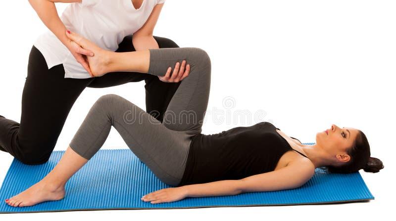 Fisioterapia - terapista che fa gamba che allunga i excercises con fotografia stock