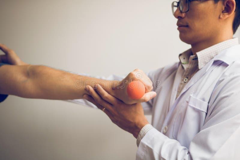 Fisioterapista asiatico le teste di legno di sollevamento d'aiuto che di un paziente funzionano con il suo recupero con i pesi ne fotografia stock libera da diritti