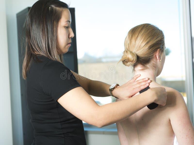Fisioterapista che applica il nastro di cinesiologia per la spalla dolorosa fotografie stock libere da diritti