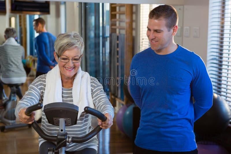 Fisioterapista che assiste donna senior nell'esercitarsi sulla bici di esercizio fotografie stock