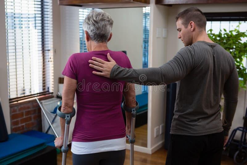 Fisioterapista che assiste il paziente senior della donna per camminare con le grucce immagine stock