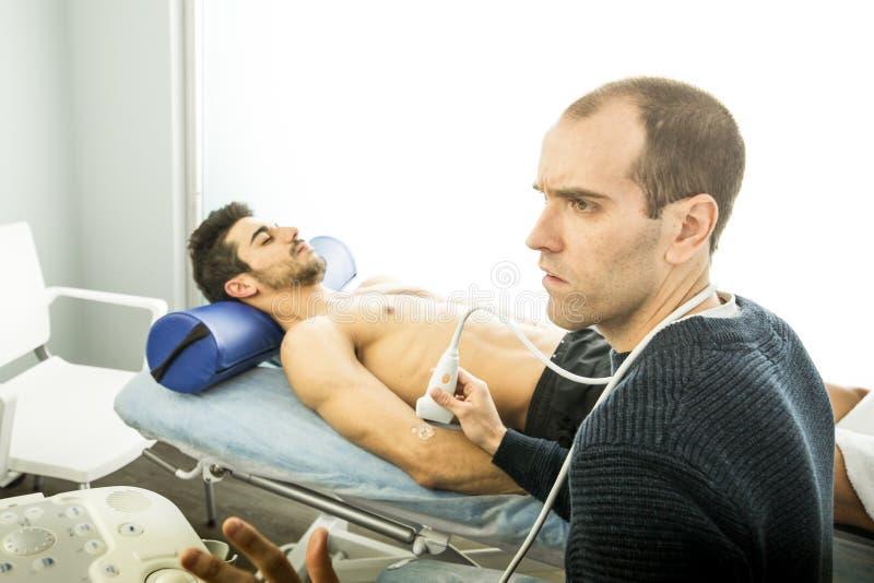 Fisioterapista che esamina un paziente con una ricerca di ultrasuono Concetto di fisioterapia avanzata del gomito fotografia stock libera da diritti