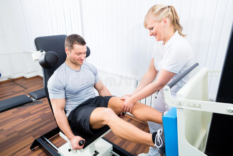 Fisioterapista che esercita paziente nella terapia di sport fotografia stock libera da diritti