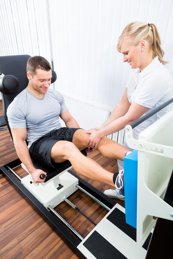 Fisioterapista che esercita paziente nella terapia di sport immagine stock libera da diritti