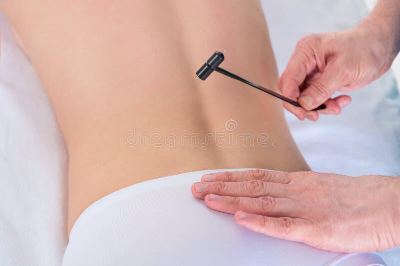 Fisioterapista che fa indietro massaggio nell'ufficio medico con un martello di agopuntura immagine stock libera da diritti