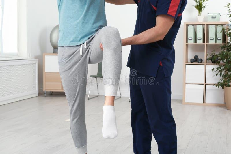 Fisioterapista che lavora con il paziente in clinica Terapia di riabilitazione fotografie stock