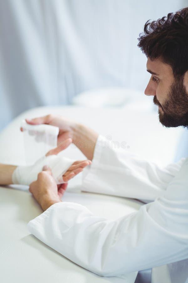 Fisioterapista che mette fasciatura sulla mano danneggiata del paziente immagine stock