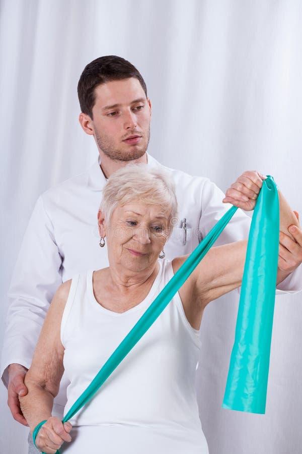 Fisioterapista che si esercita con il paziente anziano immagine stock libera da diritti