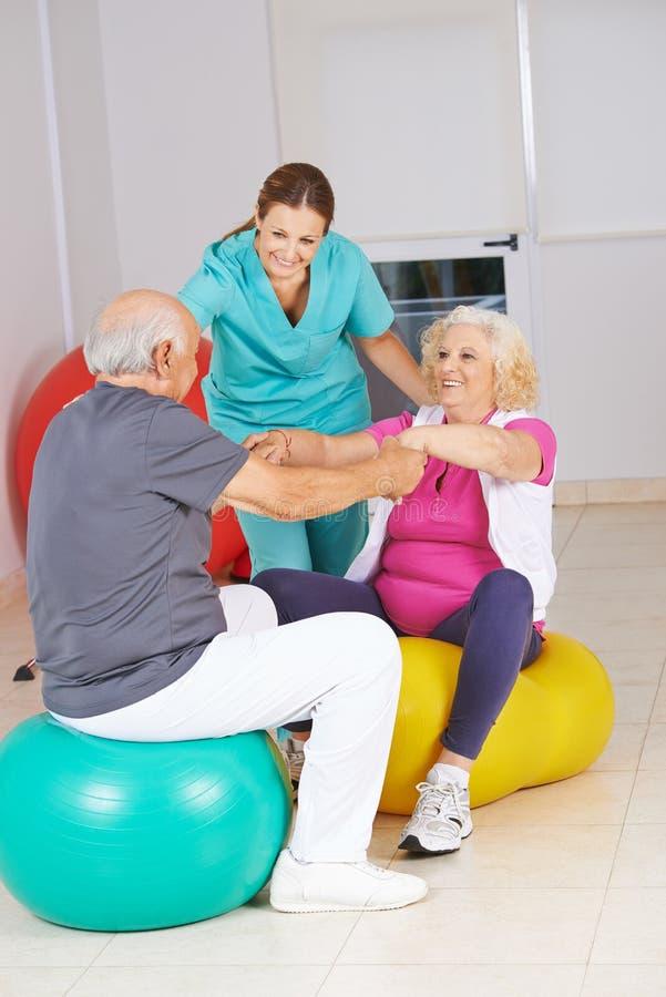 Fisioterapista con la gente senior a fisioterapia fotografia stock libera da diritti