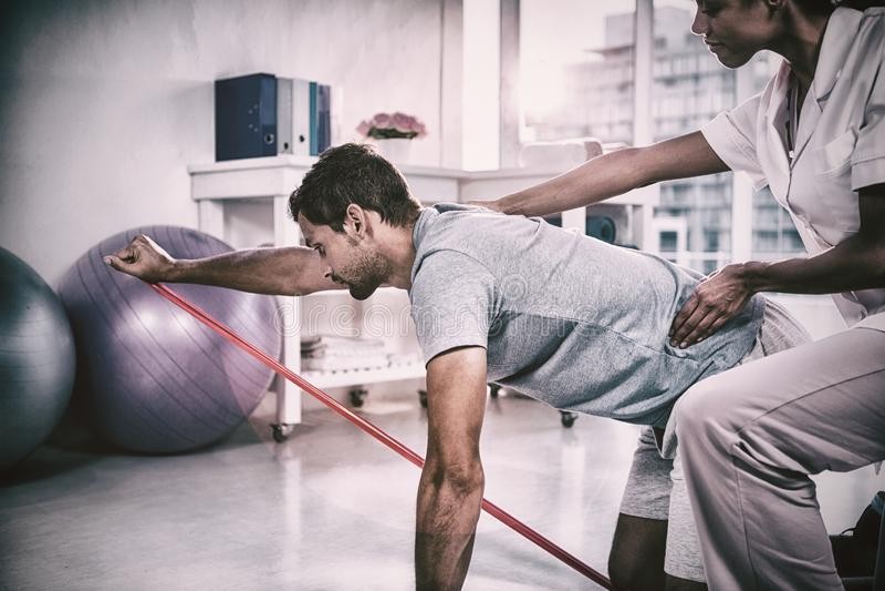 Fisioterapista femminile che assiste un paziente maschio mentre esercitandosi immagine stock
