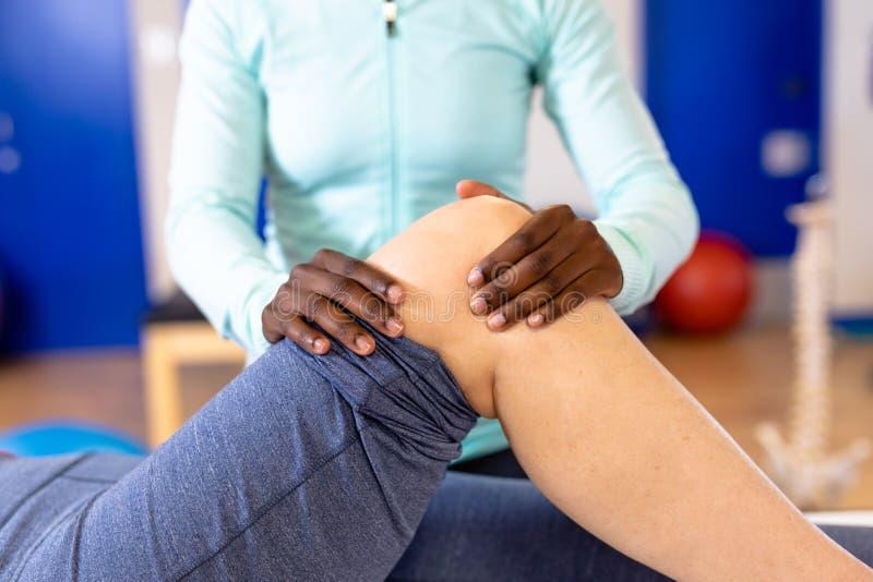 Fisioterapista femminile che dà massaggio della gamba alla donna senior attiva nel centro sportivo immagine stock libera da diritti