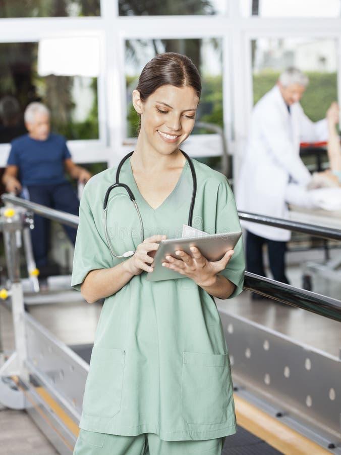 Fisioterapista femminile Using Digital Tablet al centro di forma fisica fotografia stock