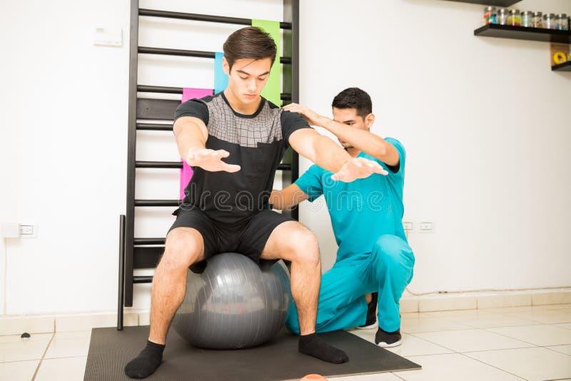 Fisioterapista Helping Man Balancing sulla palla di esercizio immagini stock