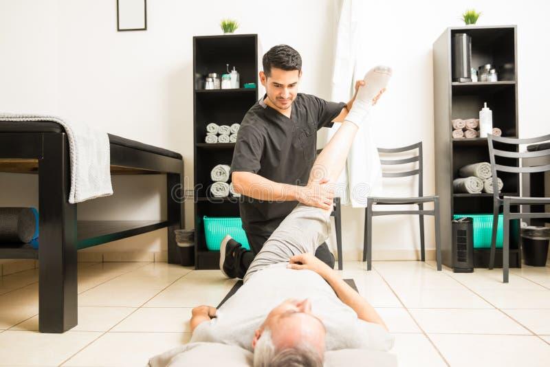 Fisioterapista Helping Mature Man con l'esercizio di gamba in clinica fotografie stock