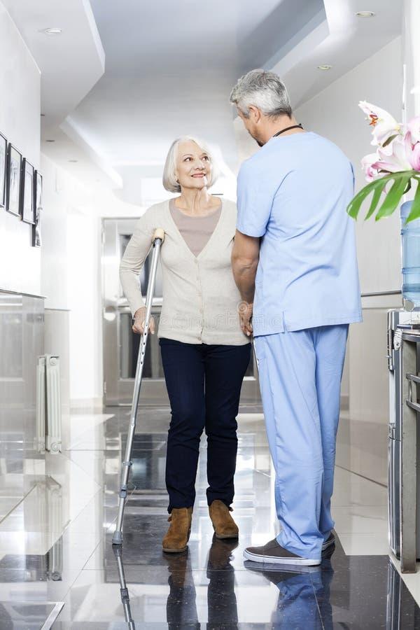 Fisioterapista Helping Senior Patient con le grucce immagine stock libera da diritti