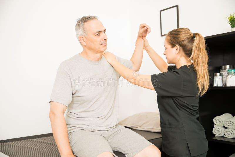 Fisioterapista Moving Injured Hand dell'uomo anziano fotografia stock