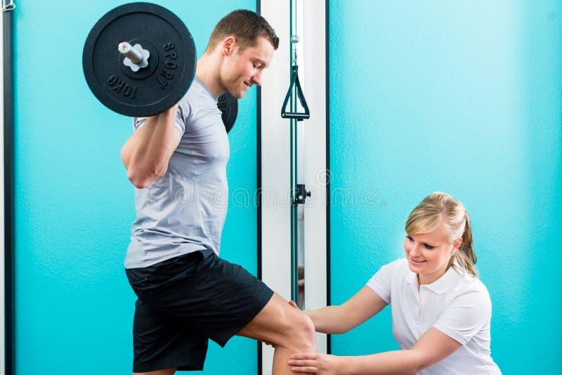Fisioterapista o medico di sport con il paziente fotografia stock libera da diritti