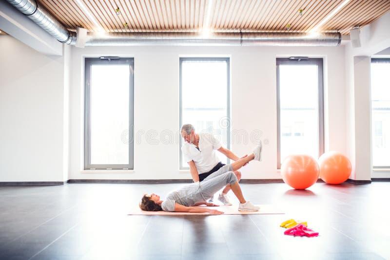 Fisioterapista senior che lavora con un paziente femminile fotografia stock