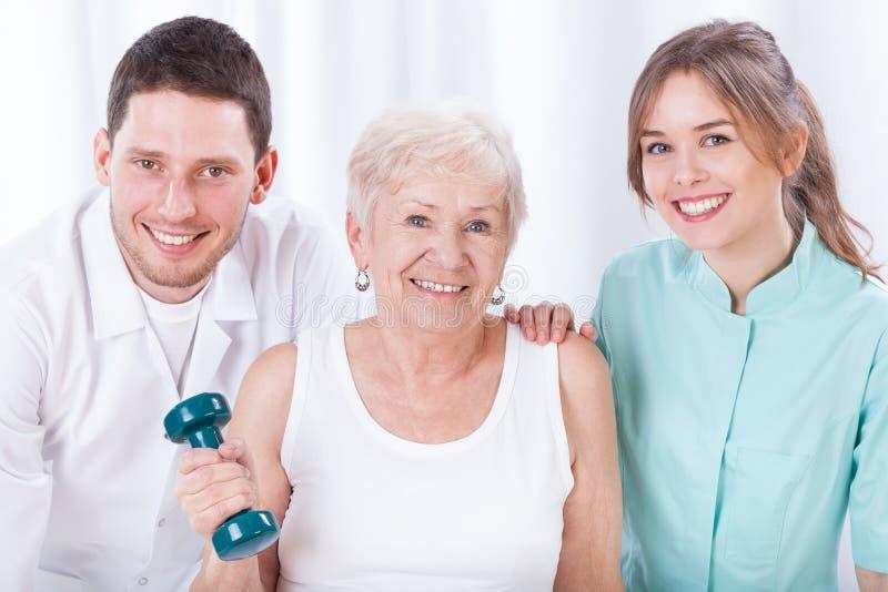 Fisioterapisti ed esercitare donna anziana immagini stock libere da diritti