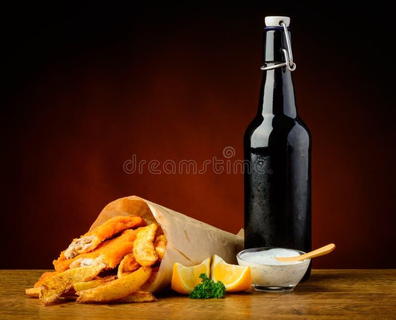 Fisk, chiper och ölflaska royaltyfri foto