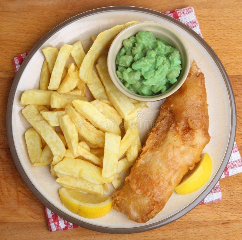 Fisk, chiper och Mushy Peas arkivbild
