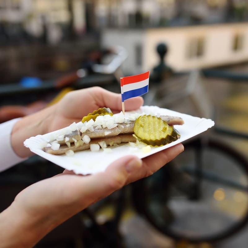 Fisk för sill för kvinnahållplatta berömd med löken och gurkan i fastfoodmarknad av Amsterdam, Nederländerna royaltyfri bild