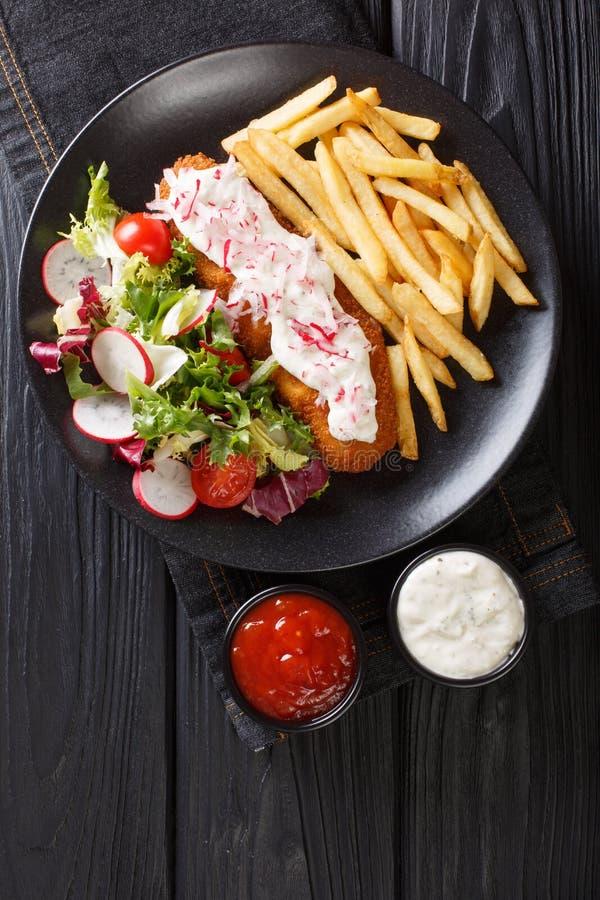 Fisk, i att panera med en sidomatr?tt av franska sm?fiskar och den nya salladn?rbilden Vertikal b?sta sikt arkivbild
