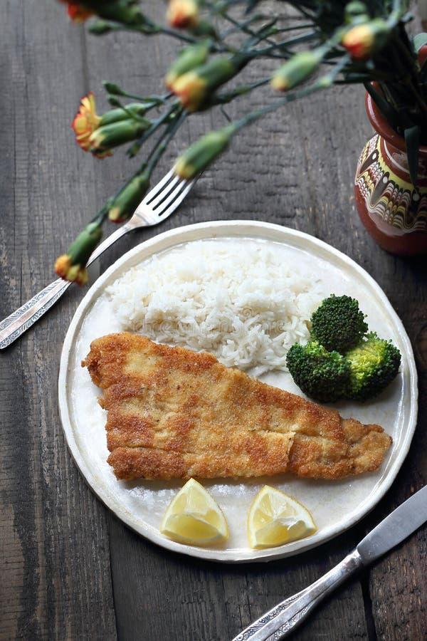 Fisk i brödsmulor som stekas i olja med ris och broccoli royaltyfri bild